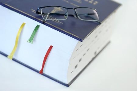 gafas de lectura: Grueso libro azul con marcadores una gafas para leer  Foto de archivo