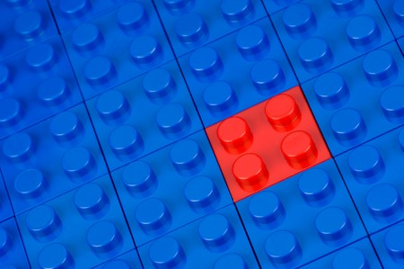 Red building block in a field of blue one Stock Photo - 7764101