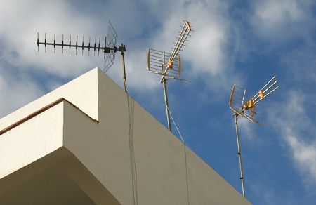 the antennae: Old fashiones radio antennae on a house roof Stock Photo