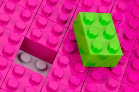 an insertion: Green building block in a field of pink one