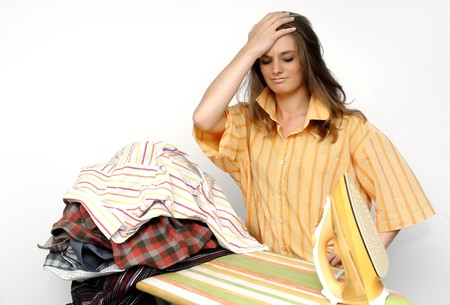 listless: Young frustrated woman at a ironing board Stock Photo