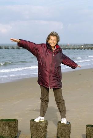 Happy active senior woman on a beach walk