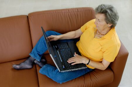 Senior woman with laptop on a couch photo