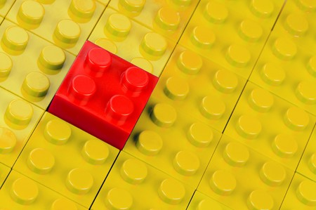 amend: Red building block in a field of yellow ones