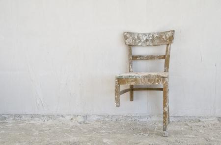 muro rotto: Vecchia sedia rotta in un cantiere