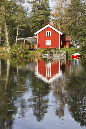시골집: 물에서 부두와 레드 코티지 스톡 사진