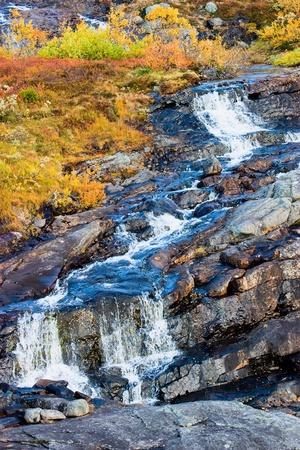 Waterfall in autumn colored landscape photo