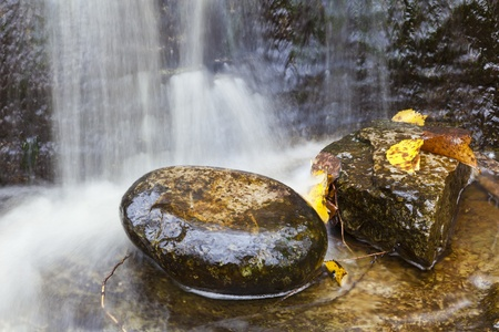 Waterfall with autumn leaves in the water, long exposure time