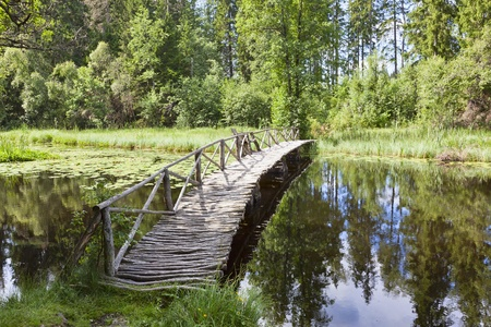 Wooden bridge over river with a bench to rest photo