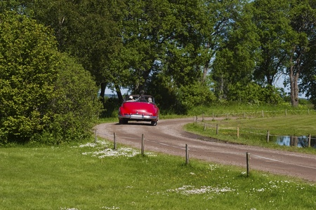 Old classic convertible car on a gravel road photo