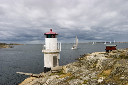 Lighthouse and sailing boats at the coast Stock Photo - 12102344