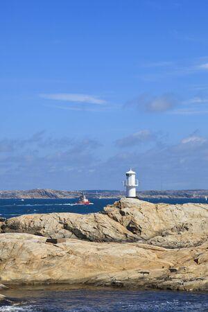 Tugboat and lighthouse at sea archipelago photo