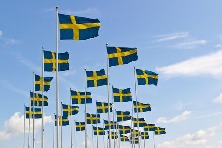 flagpoles: Swedish flag sway in the breeze against the sky
