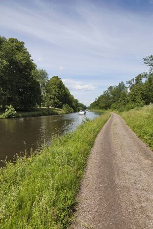 Gravel road along the Canal with boats photo