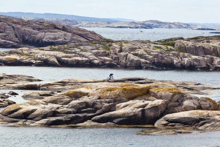 Cyclist on the rocks in the sea islands Stock Photo - 13672482