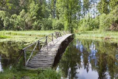 Wooden bridge over river with a bench to rest Imagens