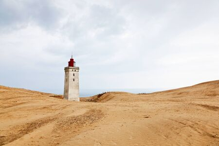 Rolling sand dune landscape and a lighthouse photo