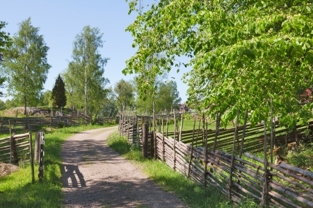 Gravel road in country side landscapes with a wooden fence