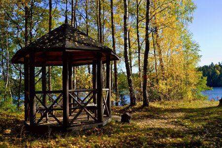 Wooden pavilion in the autumn garden photo