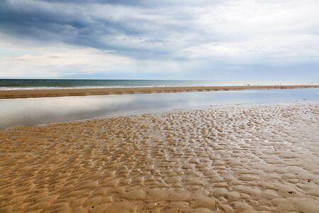 Sand beach with the ocean in the horizon and the storm clouds in the sky Stock Photo - 14508521