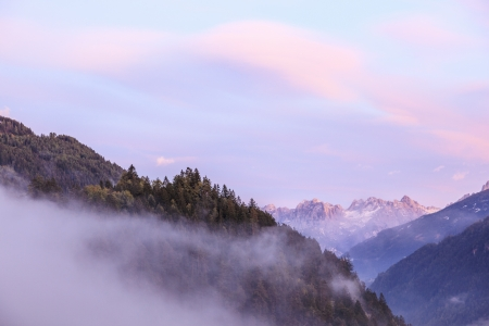 osttirol: Mountains with low clouds at sunset Stock Photo