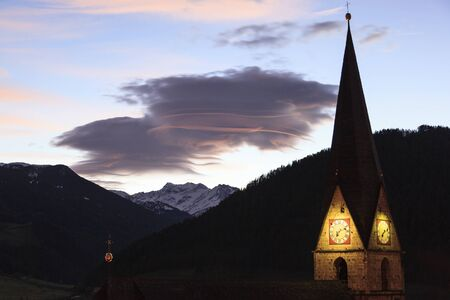 lenticular: Lenticular cloud over the Alps with an illuminated church tower Stock Photo