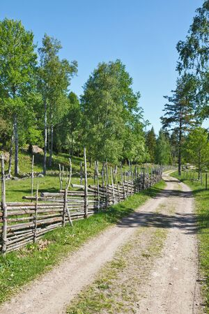 Gravel road in country side landscapes with a wooden fence. photo