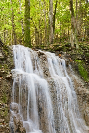 Waterfall with a stream in the deciduous forest photo