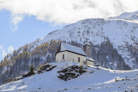 Small chapel on a hill in the Alps photo