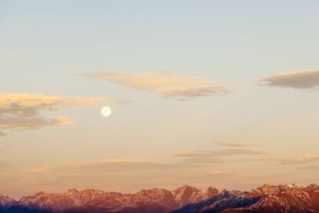 Sunset over the mountain peaks with full moon photo