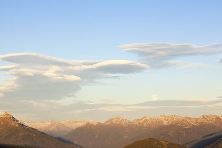 lenticular: Lenticular clouds over mountain peaks in apls at sunset Stock Photo