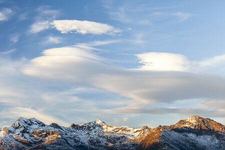lenticular: High mountain peaks with lenticular clouds Stock Photo