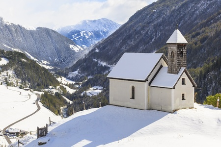 Chapel on the hill in mountain landscape photo