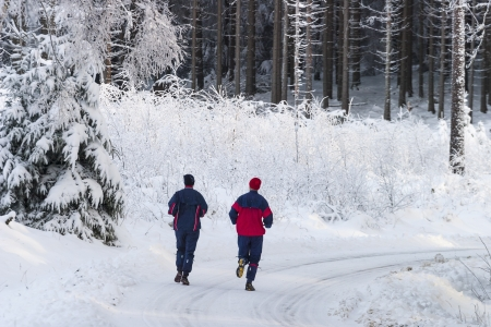 Man and woman running on a winter road photo