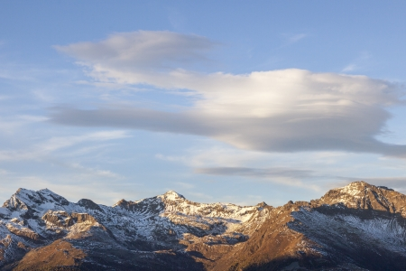 lenticular cloud: Lenticular clouds over mountain peaks Stock Photo