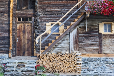 Old Alphus with flowers and a firewood pile