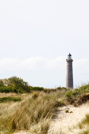 Lighthouse among sand dunes on the coast photo