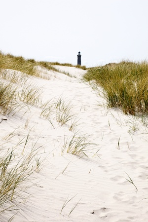 A path among sand dunes to the lighthouse photo