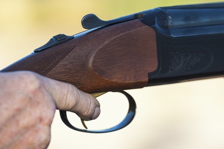 Finger on the trigger of a shotgun photo