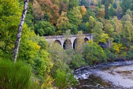 Old stone bridge in autumn landscape photo