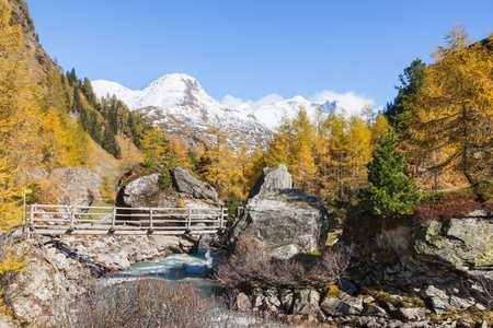 Footbridge over a river in the valley photo