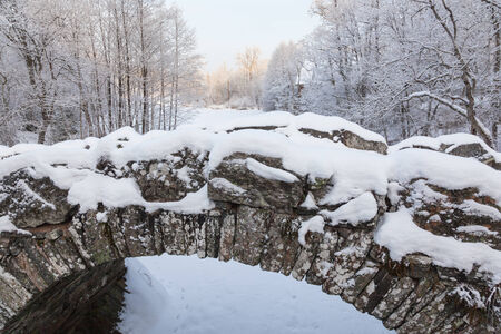 Old arch bridge over the river in the wintery landscape Stock Photo