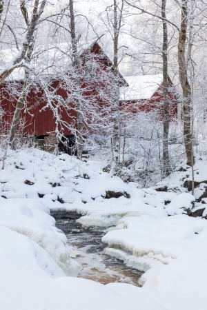 Barns at a river with snow and ice photo