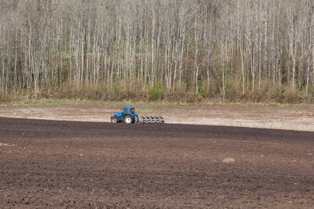 Tractor plowing the field in early spring photo