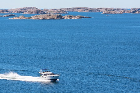 motorboat: Rocky archipelago with a motorboat at sea
