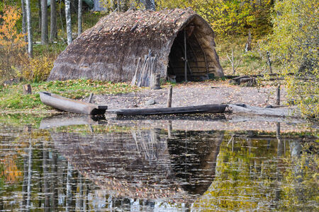 �ge de pierre: Stone Age hutte de roseaux avec des pirogues sur la plage