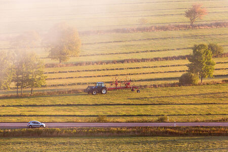 autumn road: Tractor with a tedder on the field