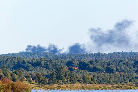 forest fire: El humo de un incendio forestal sobre el lago y el bosque