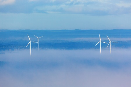 wind energy: Wind powers in misty countryside landscape Stock Photo