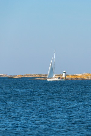sailingboat: Sailboat sailing in the archipelago with a lighthouse on the rocks